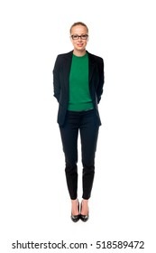 Full body portrait of beautiful smart young businesswoman in business attire wearin black eyeglasses, standing with arms behind her back against white background.