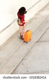 Full body portrait from behind of young woman with suitcase and mobile phone