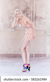 Full body portrait of blond female dressed in a light pink summer dress.