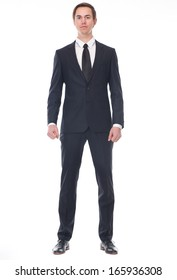 Full body portrait of a businessman in black suit standing on isolated white background