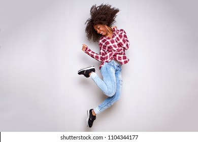 Full body portrait of cheerful young african woman jumping in air over white background