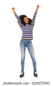 Full body portrait of cheerful young black woman cheering with arms raised against isolated white background