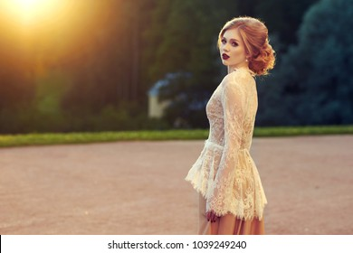 Full body portrait of elegant gorgeous young blonde woman wearing fashionable long dress and white lace jacket walking in park or garden against streetlight and shrub with green foliage on background.