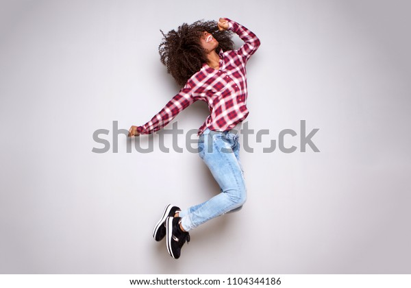 Full body portrait of excited young woman jumping in air against white background