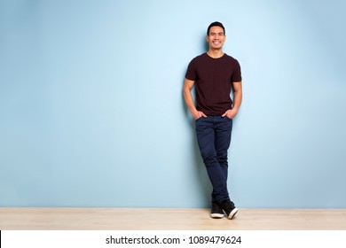 Full body portrait of fashionable asian man standing with hands in pocket by the blue wall