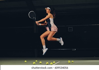 Full body portrait of female tennis player in a jump on a tennis court over dark background.
