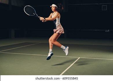 Full body portrait of female tennis player in action in a tennis court indoor.