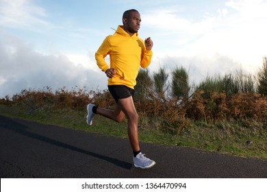 Full body portrait of fit young black guy running on street