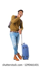 Full body portrait of handsome young african american man standing with luggage and talking with mobile phone against isolated white background