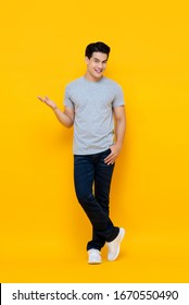 Full body portrait of handsome young Asian man smiling and standing with open hand gesture isolated on yellow background