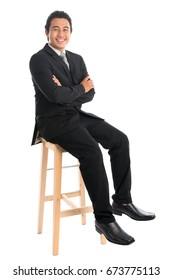 Portrait complet du jeune homme d'affaires d'Asie du Sud-Est, assis sur une chaise haute, isolé sur fond blanc.