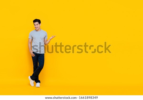 Full body portrait of handsome young Asian man smiling and standing with open hand gesture isolated on yellow background with copy space