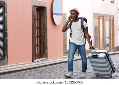 Full body portrait of happy african american tourist walking with suitcase and talking on mobile phone