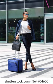 Full body portrait of a happy business woman walking with suitcase at airport