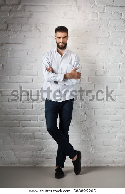 Full body portrait of happy casual bearded man standing against white brick wall, arms crossed and smiling.
