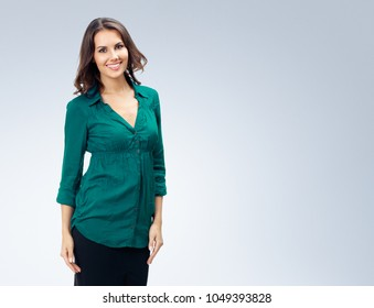 Full body portrait of happy smiling young business woman in green confident clothing, empty copyspace area for slogan or advertising text message, over grey background