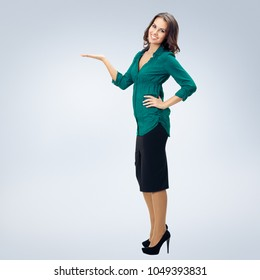 Full body portrait of happy smiling beautiful woman in green confident clothing showing something or empty copyspace area for slogan or advertising text message, over grey background. Success concept.