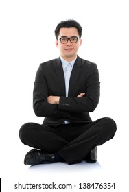 Full body portrait of happy smiling Asian business man sitting on floor, isolated on white background