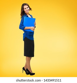 Full body portrait of happy smiling confident business woman holding blue folder with copy space, isolated over yellow orange background. Brunette dark heared model at studio.