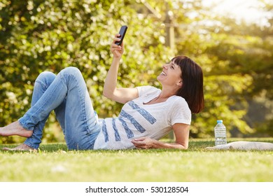 Full body portrait of happy woman lying in grass taking selfie with smart phone