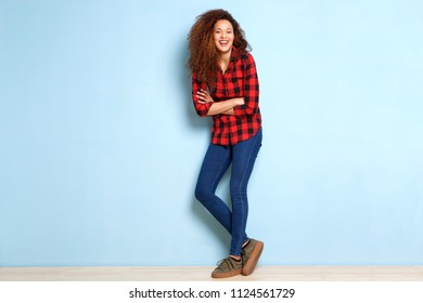 Full body portrait of happy young woman leaning against blue wall