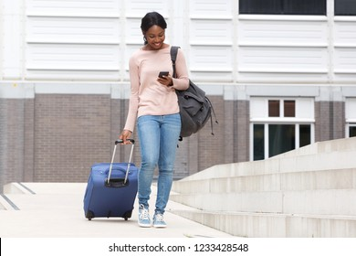 Full body portrait of happy young african american woman walking with suitcase bag and cellphone