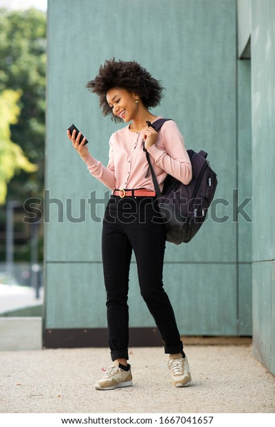 Full body portrait happy young African american woman walking with phone and bag