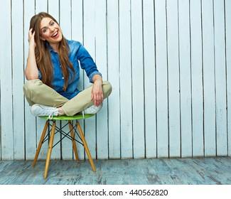 Full body portrait of hipster girl sitting on chair. White wooden  plank background.