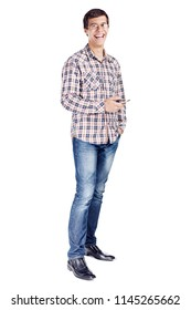 Full body portrait of laughing young man with mobile phone in hand, other hand in pocket wearing metal frame glasses, checkered shirt, blue jeans and black shoes isolated on white background