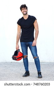 Full body portrait of motorcyclist with helmet and ripped jeans
