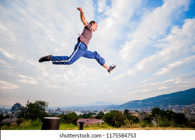 Full body portrait of parkour man jumping high in the park with copy space