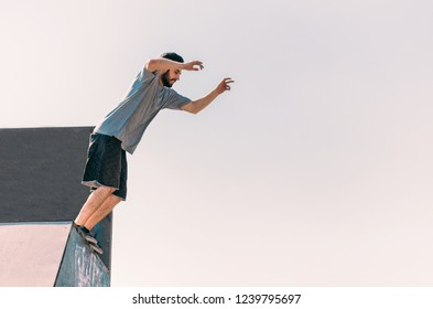 Full body portrait of parkour man jumping high in the skate-park