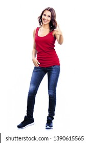 Full body portrait photo - young smiling woman in casual clothing, blue jeans, showing thumbs up gesture, isolated on white background. Happy girl in red t-shirt. Brunette Model at studio picture.