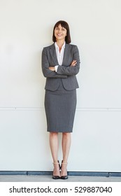 Full body portrait of professional business woman standing with arms crossed by white wall