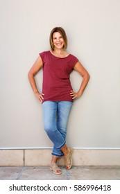 Full body portrait of senior woman smiling against wall