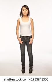 Full body portrait of a serious young Asian female model in white tank top and jeans standing in light studio and looking at camera. She is looking confident and strong.