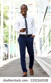 Full body portrait of smiling african american businessman walking on city street with cellphone