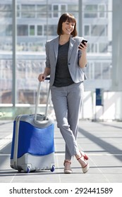 Full body portrait of a smiling business woman standing with mobile phone and bag at airport