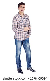 Full body portrait of smiling young man with mobile phone in hand, other hand in pocket wearing metal frame glasses, checkered shirt, blue jeans and black shoes isolated on white background