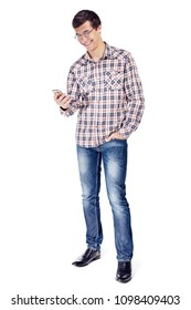 Full body portrait of smiling young man with hand in pocket reading text message on mobile phone wearing metal frame glasses, checkered shirt, blue jeans and black shoes isolated on white background