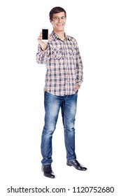 Full body portrait of smiling young man showing mobile phone, other hand in pocket wearing metal frame glasses, checkered shirt, blue jeans and black shoes isolated on white background