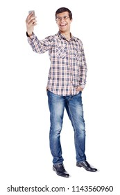 Full body portrait of smiling young man taking selfie on mobile phone wearing metal frame glasses, checkered shirt, blue jeans and black shoes isolated on white background