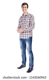 Full body portrait of smiling young man with mobile phone in hands, wearing metal frame glasses, checkered shirt, blue jeans and black shoes isolated on white background