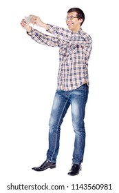 Full body portrait of smiling young man taking photo with smartphone wearing metal frame glasses, checkered shirt, blue jeans and black shoes isolated on white background