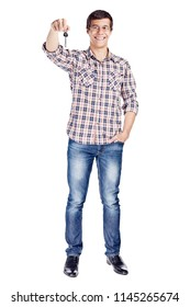 Full body portrait of smiling young man showing new house key, other hand in pocket wearing metal frame glasses, checkered shirt, blue jeans and black shoes isolated on white background