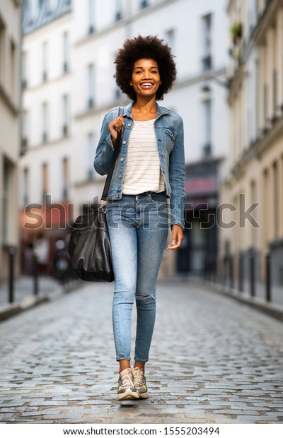Full body portrait of smiling young african american female fashion model walking on street in city