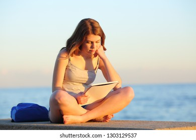 Full body portrait of a studious student studying reading notes sitting on a bench on the beach