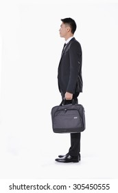 Full body Portrait of a successful young business man carrying a suitcase walking on white background