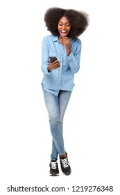Full body portrait of surprised young woman looking at mobile phone
