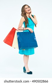 Full body portrait of surprised young woman with shopping bags. Smiling female model isolated  on white background.